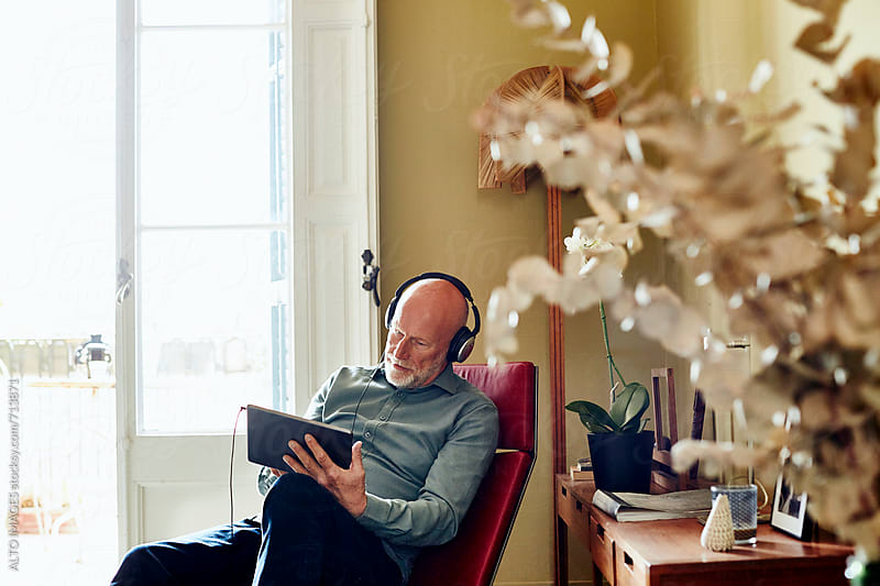 Happy Senior Man Listening Music On Digital Tablet by ALTO IMAGES for Stocksy United
