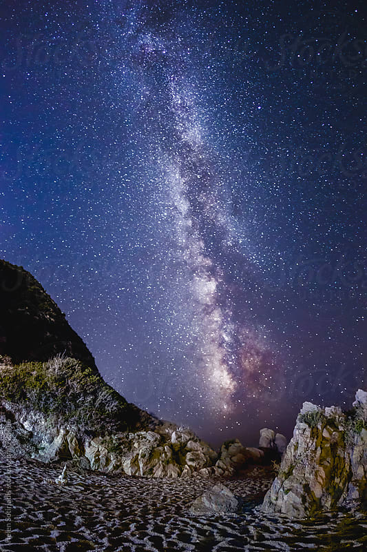 The Milky Way over a Rocky and Sandy Beach by Helen Sotiriadis for Stocksy United