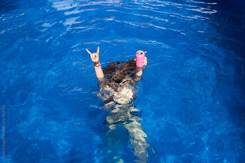Unrecognizable person showing rock and roll sign underwater and holding a beer by Guille Faingold for Stocksy United