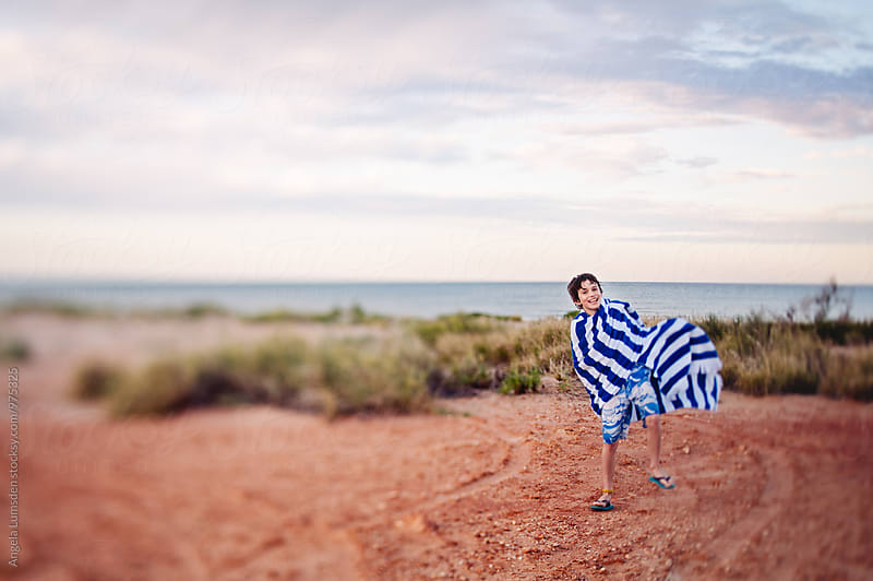 Boy in a bathing suit and blue and white striped towel near a beach in Australia by Angela Lumsden for Stocksy United