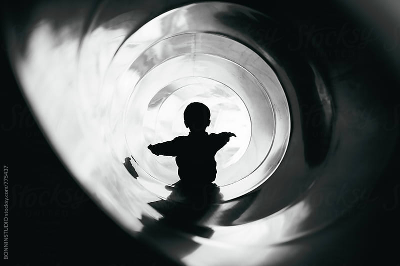 Back view of a kid playing on the slide. by BONNINSTUDIO for Stocksy United