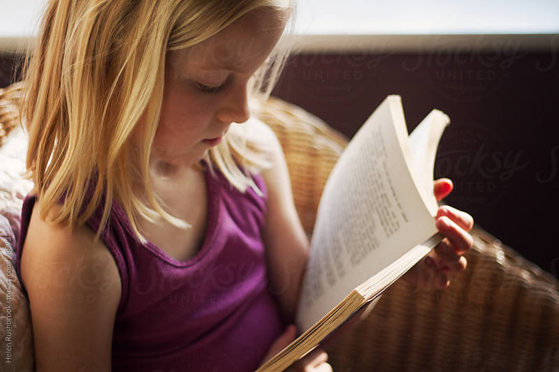 A little girl reading a book by Helen Rushbrook for Stocksy United