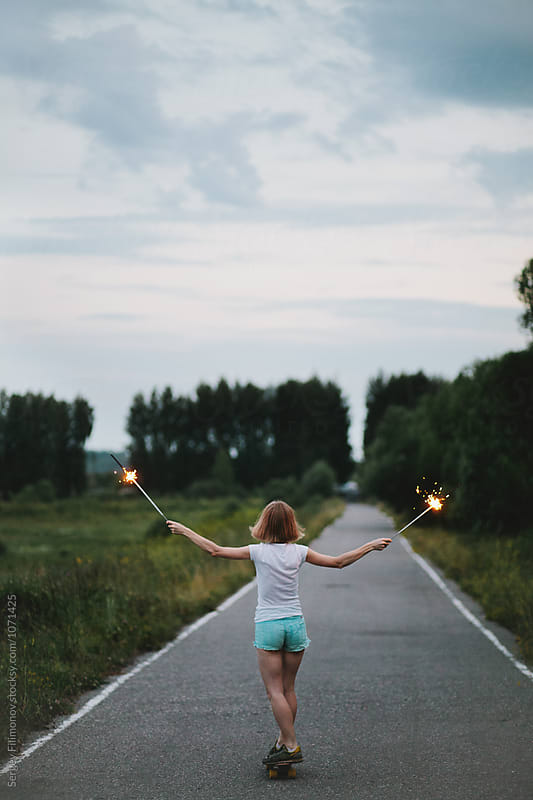 blonde girl riding on longboard with burning sparklers by Sergey Filimonov for Stocksy United