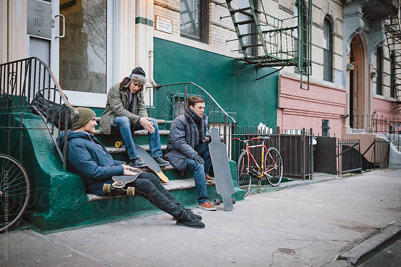 Young Men Friends Hanging Out at Front Stoop of Brooklyn Apartment Building by Joselito Briones for Stocksy United