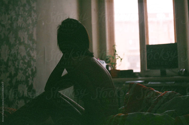A film dark portrait of a young woman in the bed by Anna Malgina for Stocksy United