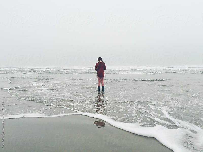 Preteen girl standing on beach, facing incoming surf and waves by Paul Edmondson for Stocksy United
