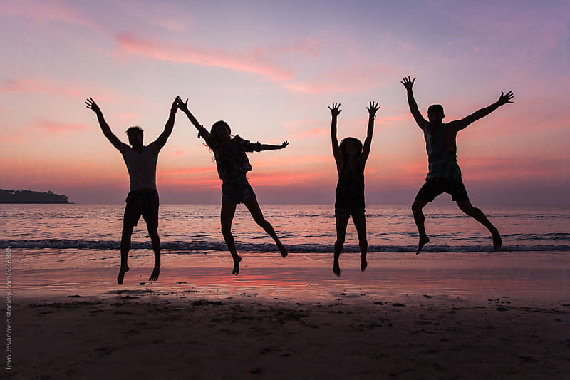 Four friends jumping together at the beach by Jovo Jovanovic for Stocksy United