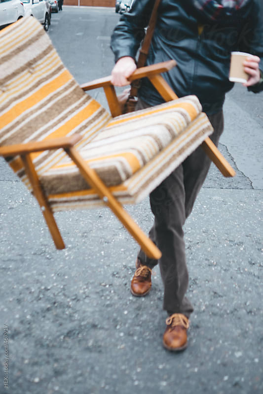 Stylish Man Carrying an Armchair on the Street by HEX. for Stocksy United
