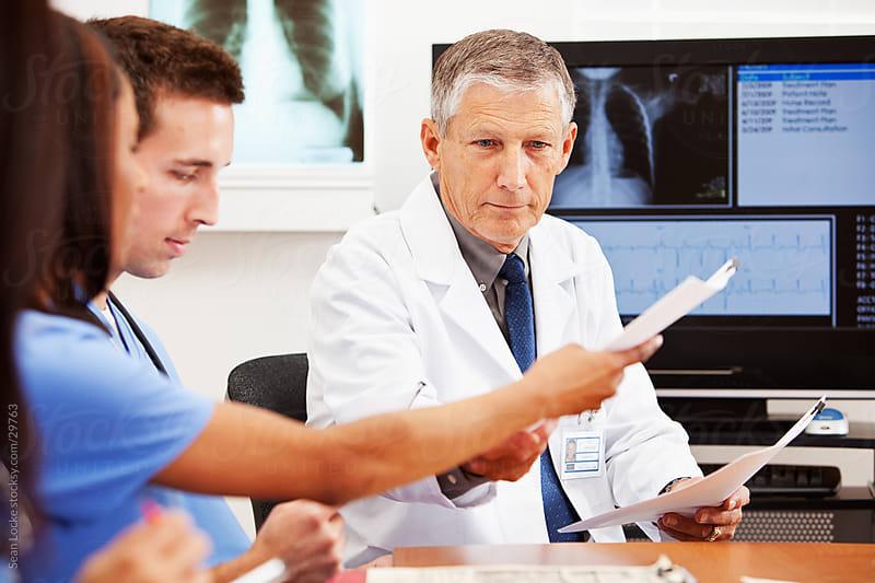 Doctors: Passing Around Paperwork by Sean Locke for Stocksy United