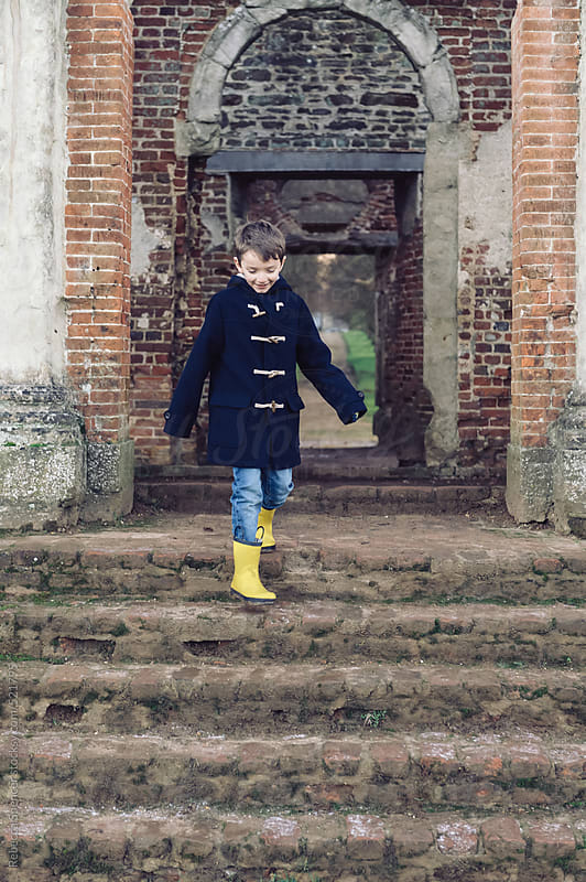 Happy child decending brick stairs outside by Rebecca Spencer for Stocksy United