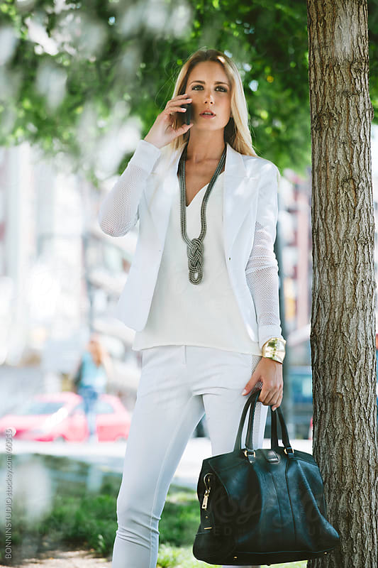 Young businesswoman talking with smartphone on the street. by BONNINSTUDIO for Stocksy United