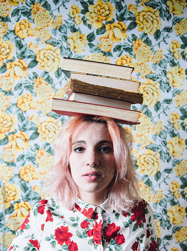 woman with a pile of books on her head by Thais Ramos Varela for Stocksy United