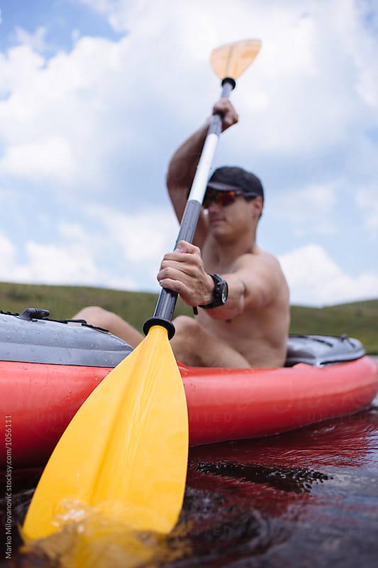 Man kayaking on lake by Marko Milovanović for Stocksy United