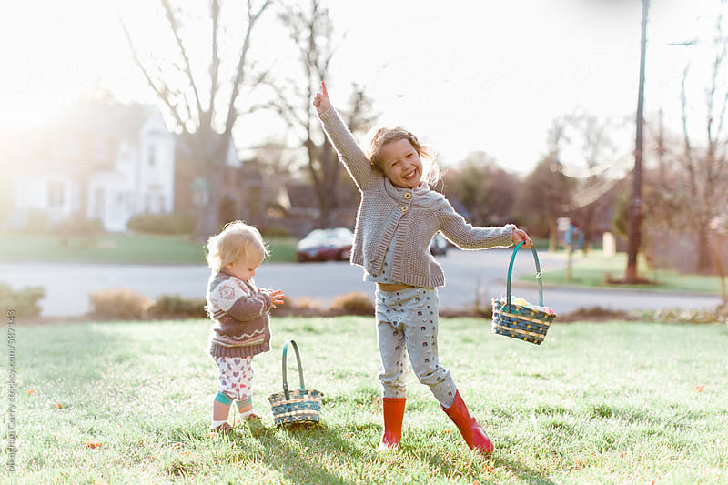 two sisters celebrate easter with an outdoor egg hunt by Meaghan Curry for Stocksy United
