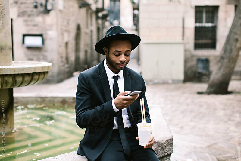 African american businessman using phone whilst eating fast food on the street. by BONNINSTUDIO for Stocksy United