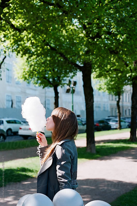 Young woman eating cotton candy outdoors. by Lyuba Burakova for Stocksy United