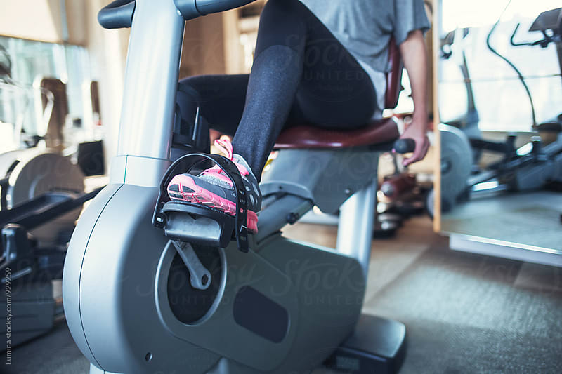Legs of Woman Working Out on a Bicycle at Gym by Lumina for Stocksy United