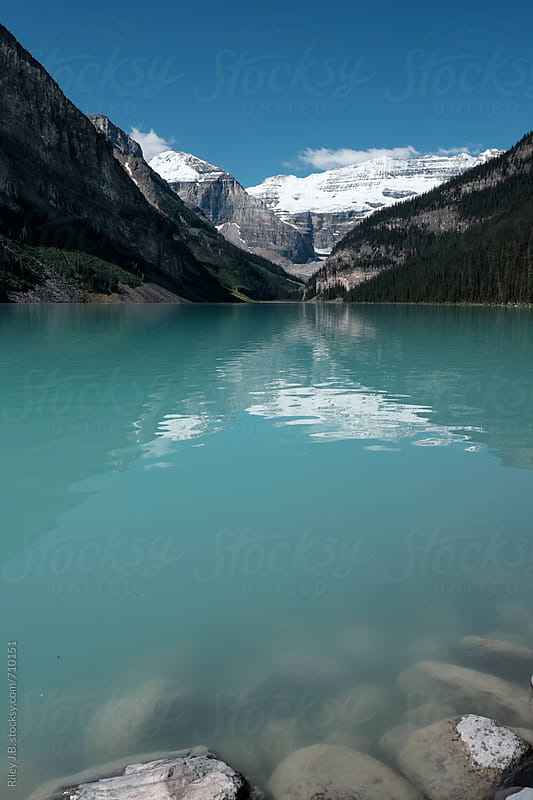 View of a glacial lake and mountains by Riley J.B. for Stocksy United