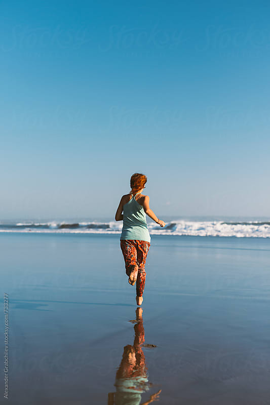 Young woman running on the beach by Alexander Grabchilev for Stocksy United