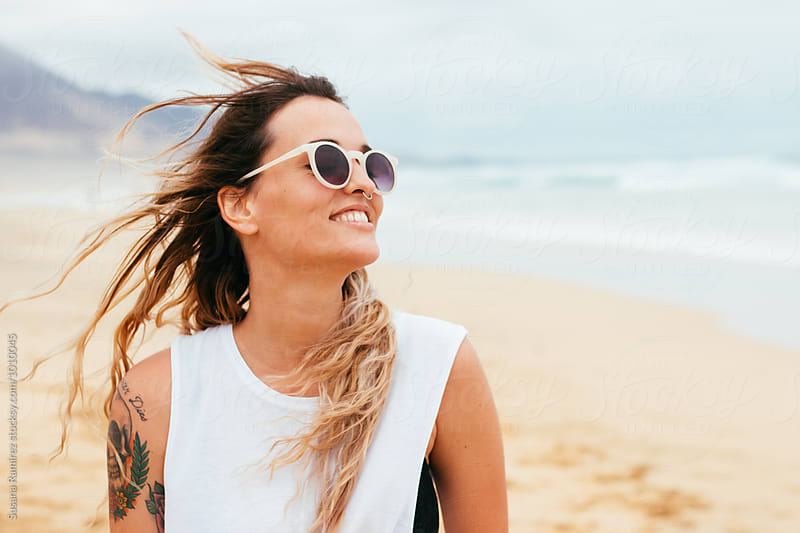 Portrait of smiling and happy woman on the beach by Susana Ramírez for Stocksy United
