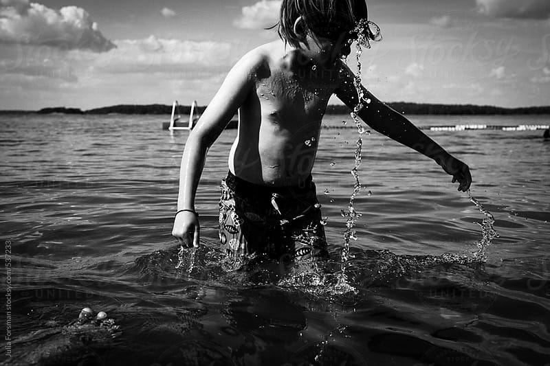 Boy with water running off him in a lake. by Julia Forsman for Stocksy United