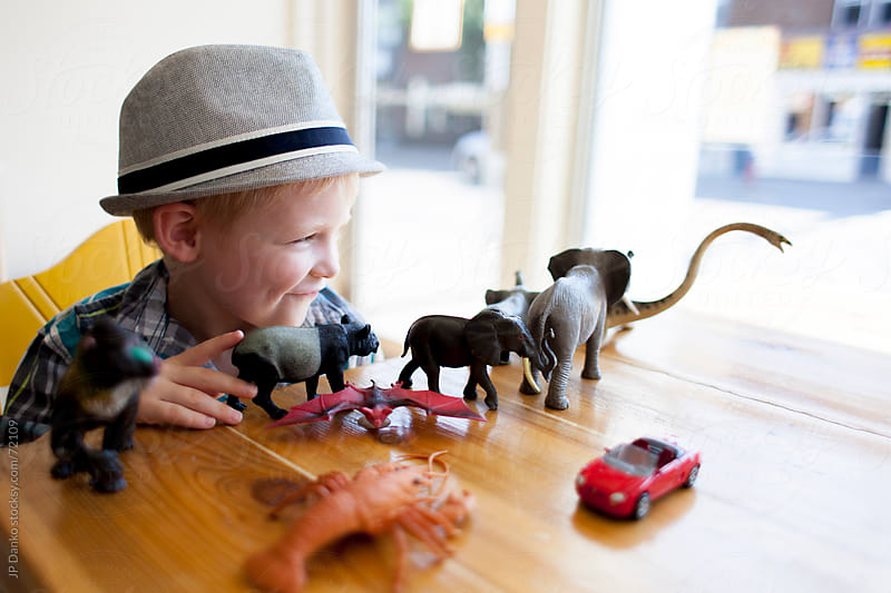 Little Boy Playing with Animal Toys at Coffee Shop by JP Danko for Stocksy United