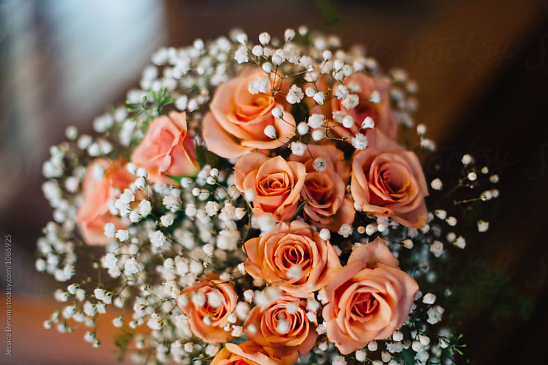 Closeup of a bridal bouquet with peach roses and baby's breath. by Jessica Byrum for Stocksy United