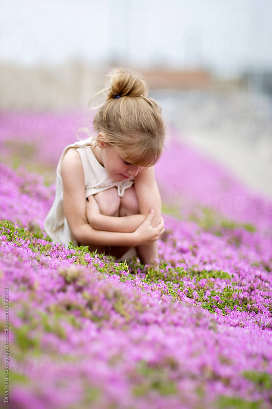 Young girl in white dress sitting in purple flowers by Dina Giangregorio for Stocksy United