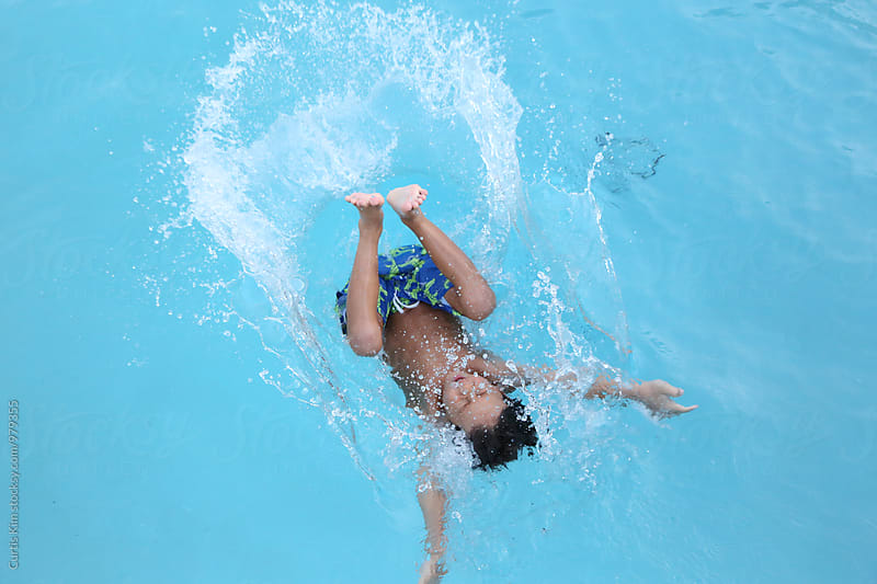 Boy splashing into pool by Curtis Kim for Stocksy United