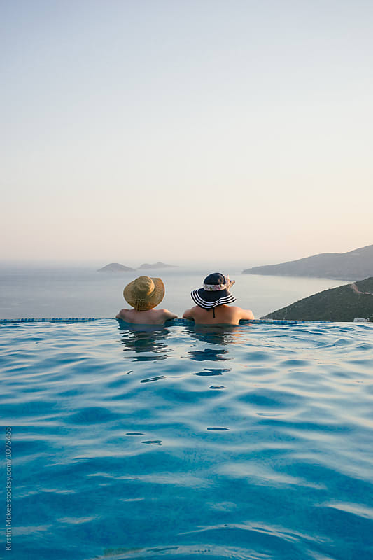 Two Best friends looking at the view from a swimming pool by Kirstin Mckee for Stocksy United