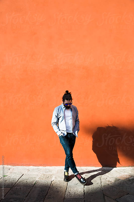 Man kicking away a stone in front of an orange wall by Beatrix Boros for Stocksy United