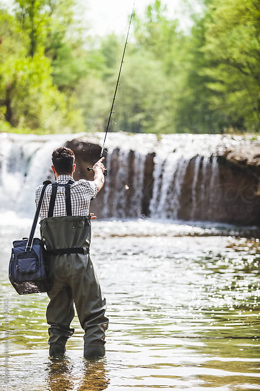Young Man with Equipment Box Fishing near a Waterfall by Giorgio Magini for Stocksy United