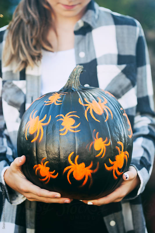 Painted: Teen Girl Holds Spider Painted Pumpkin by Sean Locke for Stocksy United