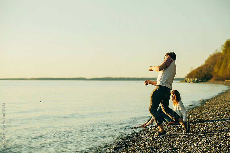 Skipping Rocks at Sunset by Willie Dalton for Stocksy United