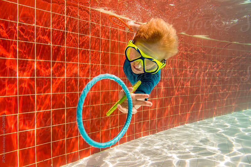 Little Boy Chasing Rings Swimming Underwater In All Inclusive Resort Pool on Caribbean Vacation by JP Danko for Stocksy United