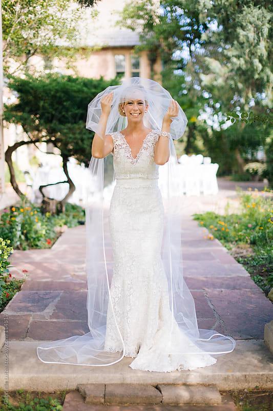 Bride in Garden Courtyard  by Gabrielle Lutze for Stocksy United