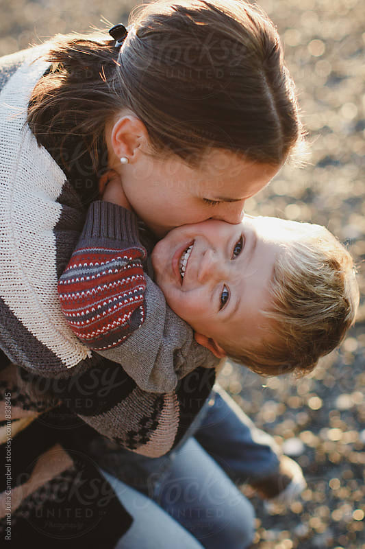 Young mom enjoying cuddling with toddler son outside at the beach by Rob and Julia Campbell for Stocksy United