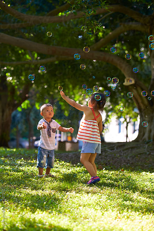 adorable kids playing with bubble outdoor in the sunny park by cuiyan Liu for Stocksy United