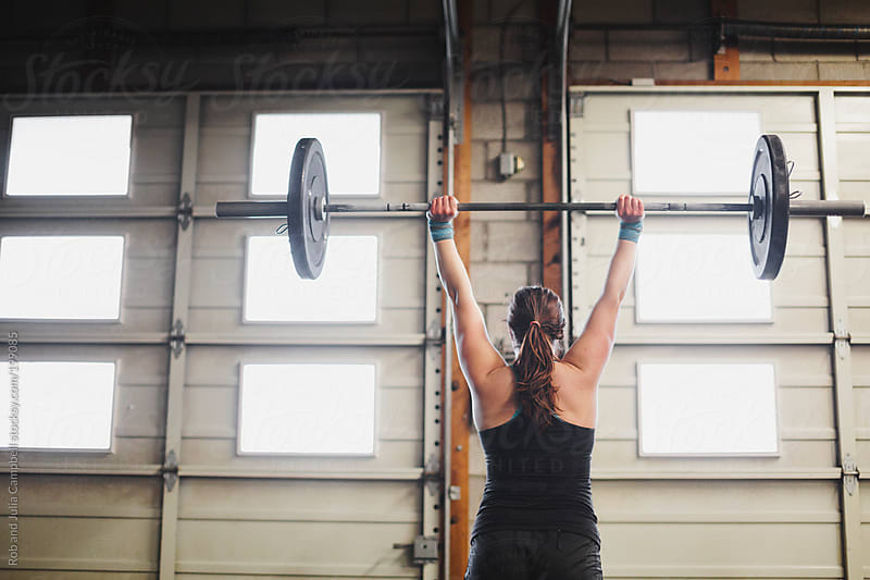 Strong young woman lifting weights in gritty gym by Rob and Julia Campbell for Stocksy United