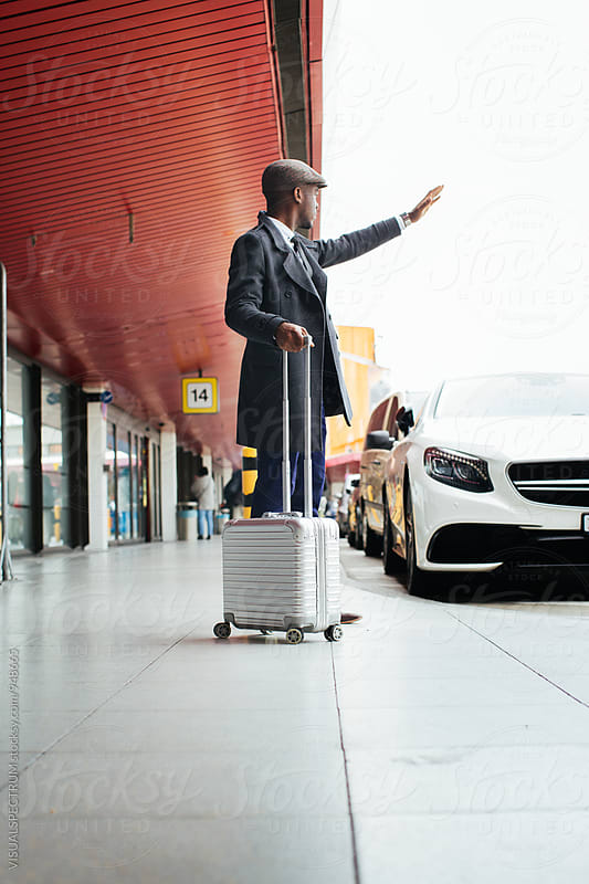 Young Stylish Black Businessman Waving Down Taxi at Airport by Julien L. Balmer for Stocksy United