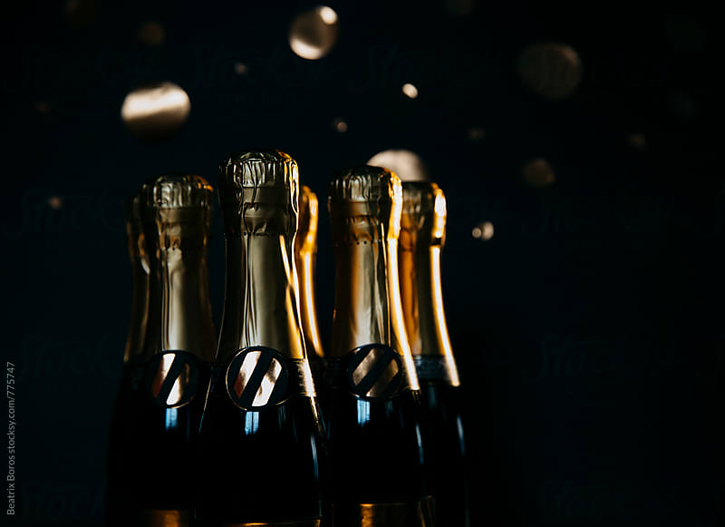 Bottles of champagne in front of black background by Beatrix Boros for Stocksy United