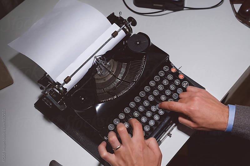 Man typing with a vintage typewriter  by RG&B Images for Stocksy United