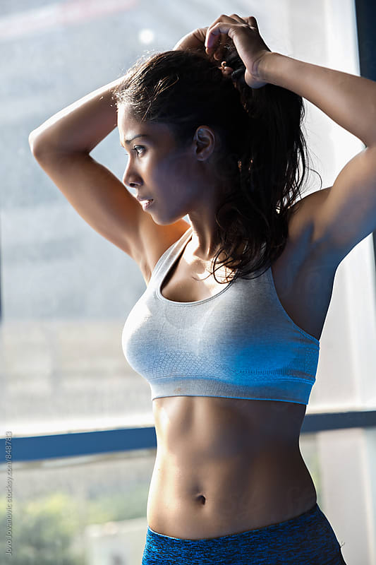 Muscly girl fixing her hair by Jovo Jovanovic for Stocksy United