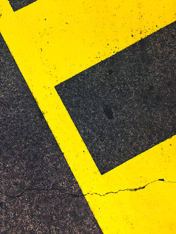 Yellow parking lines painted on the asphalt by Leandro Crespi for Stocksy United