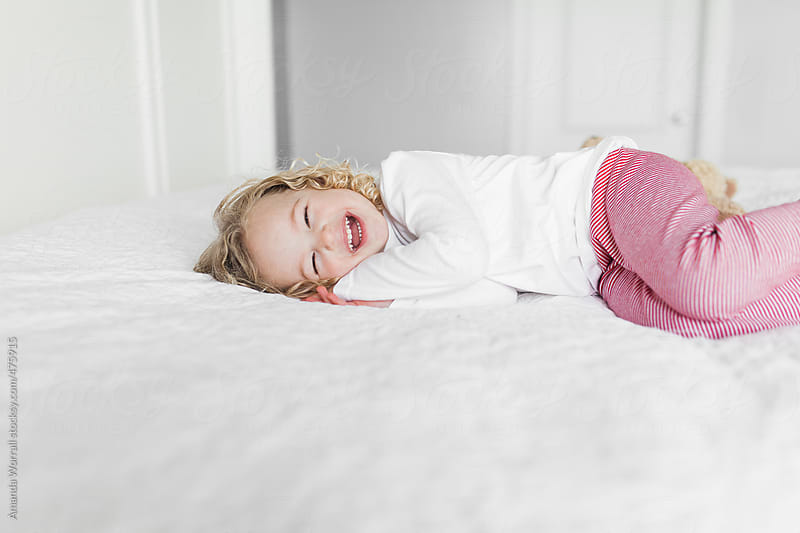 Happy young girl wearing red and white striped leggings by Amanda Worrall for Stocksy United
