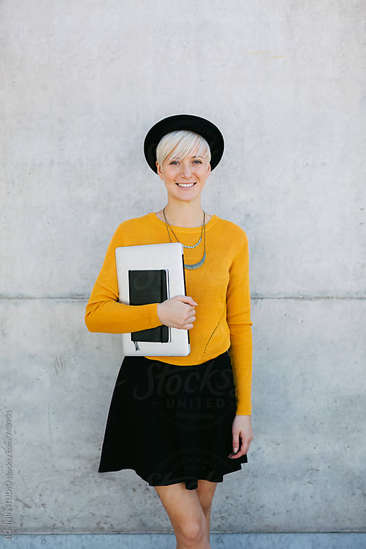 Portrait of a chic woman holding a laptop on the street. by BONNINSTUDIO for Stocksy United