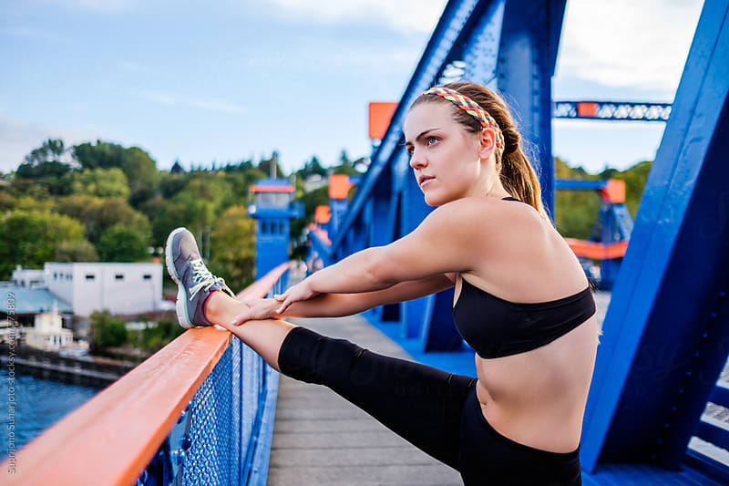 Female runner stretching in the city by Suprijono Suharjoto for Stocksy United