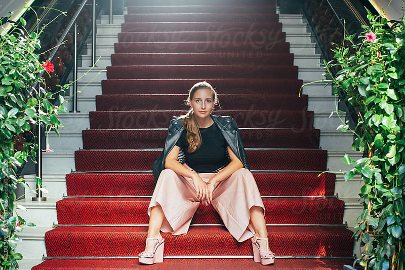 Young Fashionable Caucasian Woman Sitting on Red Carpet on Stairs by VISUALSPECTRUM for Stocksy United
