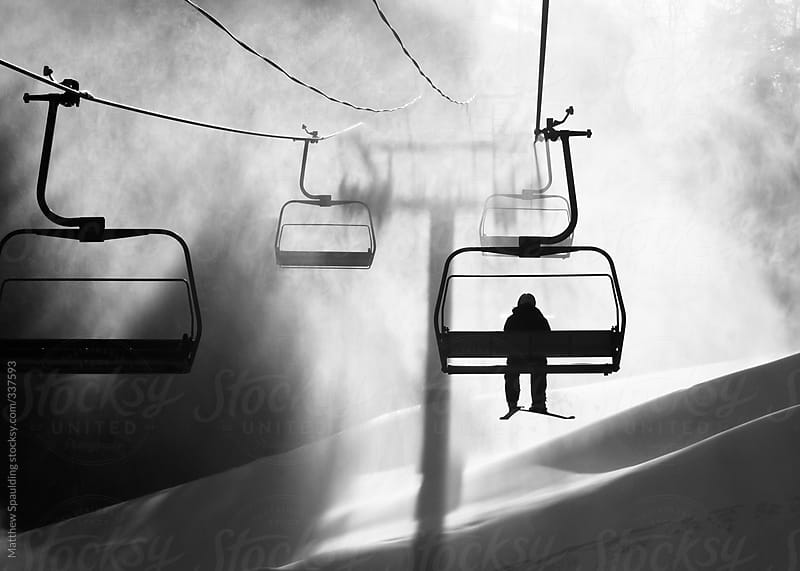Skier riding on a chairlift on a snow covered mountain by Matthew Spaulding for Stocksy United