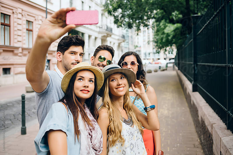Friends Taking a Selfie on the Street by Lumina for Stocksy United